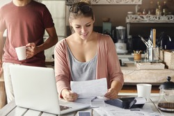 Happy beautiful woman reading notification from bank on prolongation of mortgage term while working through papers at kitchen table with laptop and calculator, her husband standing behind her