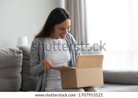 Happy beautiful woman received parcel, curious girl opening cardboard box, satisfied customer unpacking online store order, removing wrapper, looking inside, good delivery service concept