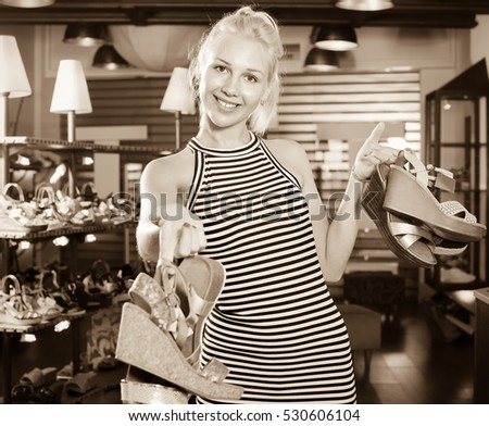 Happy beautiful  woman standing in boutique and having many shoes in hands