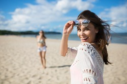 Happy beautiful woman standing on beach with friend laughing