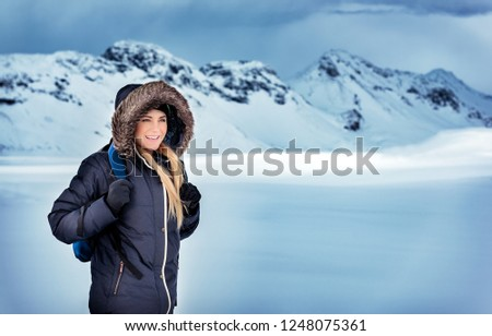 Happy beautiful woman with backpack traveling in the snowy mountains, trekking in the North Pole, extreme winter holidays, Iceland