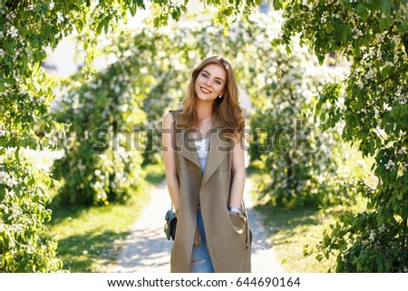 Happy beautiful woman with cute smile in fashionable clothes in the park on a spring sunny day