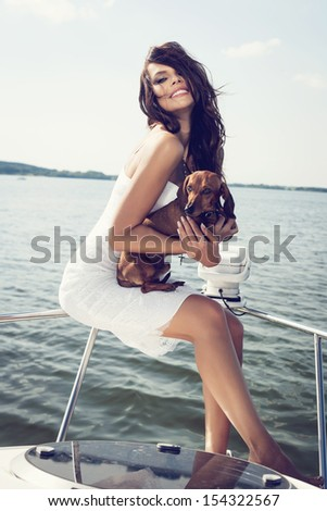 happy beautiful woman with dog on the luxury boat in open sea in summer. Caucasian female model. Outdoors, lifestyle.