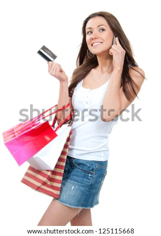 Happy Beautiful woman with shopping bags and credit gift card talking on cellular mobile phone, cheerful smiling on a white background