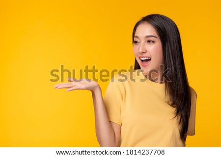 Happy beautiful young asian woman with yellow background holding copy space imaginary on beauty palm for insert advertisement, happiness and smiley face. Attractive beautiful girl portrait
