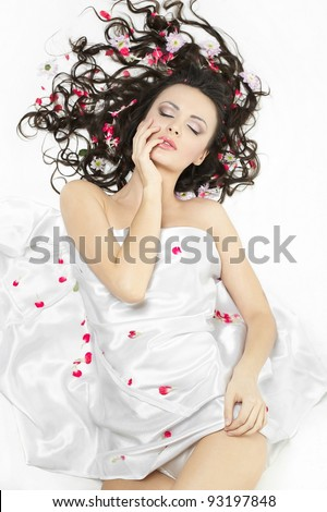 happy beautiful young brunette girl covered with bed sheet in bright flowers isolated on white