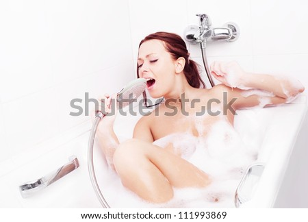 happy beautiful young brunette woman taking a relaxing bath with foam and singing