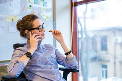 Happy beautiful young business woman in glasses sitting and talking on cell phone in office