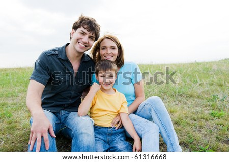 Happy beautiful young family posing outdoors. Three people - stock photo
