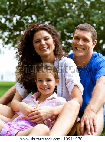 Happy beautiful young family sitting on the green grass. Three cheerful person