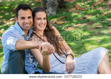 Happy beautiful young man and woman in love, lying on grass in park and relaxing