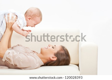 happy beautiful young mother and baby laying on sofa