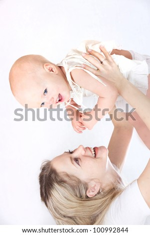 happy beautiful young mother holding her laughing little baby up isolated on white background in studio