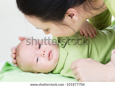 happy beautiful young mother with her little baby in studio