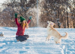 Happy beautiful young woman blowing snowflakes from her hands to her dog golden retriever in a winter day. Friendship, pet and human.