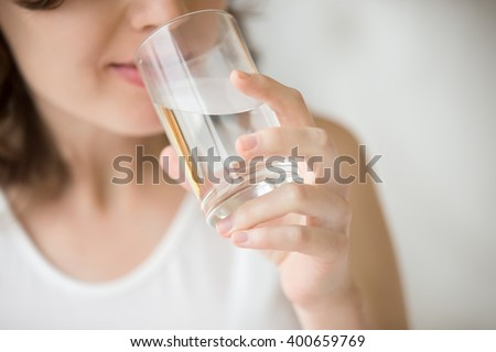 Happy beautiful young woman drinking water. Smiling caucasian female model holding transparent glass in her hand. Closeup. Focus on the arm
