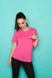 Happy beautiful young woman in pink shirt is pointing at herself and talking. Three quarter length studio shot on turquoise background.