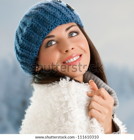 Happy beautiful young woman in warm soft clothes outdoor in a winter day