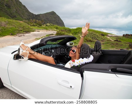 Happy beautiful young woman sitting in a sports car on beautiful summer day. Sexy woman's legs showing out of the car, enjoying freedom feeling happy on the Hawaii.  #258808805