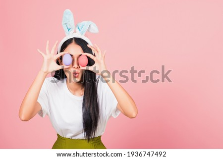 Happy beautiful young woman smiling wearing rabbit ears holding colorful Easter eggs front eyes, Thai female with bunny ear hold easter egg covering eye, studio shot isolated on pink background