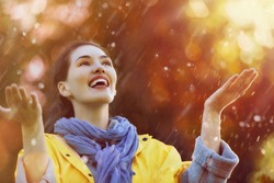 Happy beautiful young woman under the autumn shower. Girl is wearing yellow raincoat and enjoying rainfall.