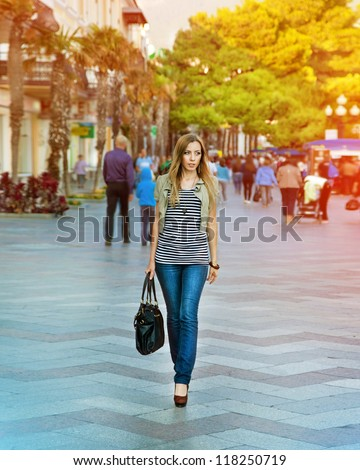 Happy beautiful young woman walking on the street