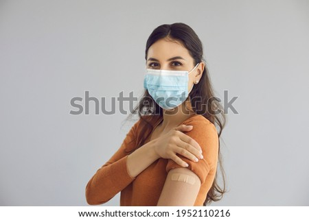 Happy beautiful young woman wearing medical face mask isolated on gray copy space background shows adhesive plaster on arm after getting safe Covid 19 vaccine. Coronavirus vaccination campaign concept
