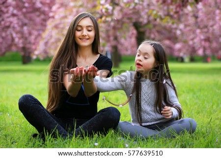 Happy beautiful young woman with girl in blossom park with trees and flowers.