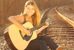 Happy Beautiful Young Woman With Guitar On Railroad Tracks. Copy Space. Pretty smiling young lady holding guitar on railway.