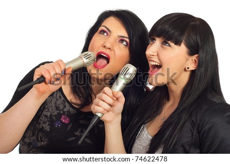 Happy beauty two women singing in microphones at karaoke party and looking up to screen isolated on white background