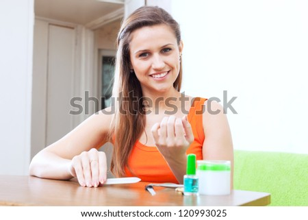 Happy beauty woman looks at nails at home