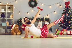Happy beginner athlete in funny underwear and Santa hat made New Year resolution to keep fit and healthy and is doing supine side leg raises with dumbbells during home workout on Christmas holidays
