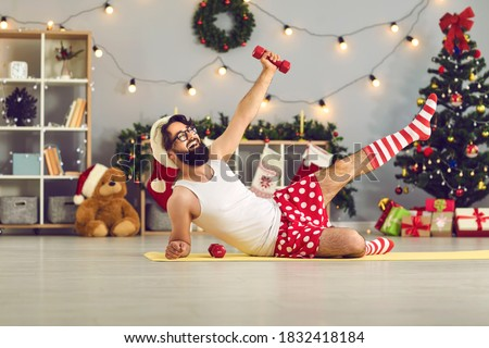 Happy beginner athlete in funny underwear and Santa hat made New Year resolution to keep fit and healthy and is doing supine side leg raises with dumbbells during home workout on Christmas holidays Foto stock ©