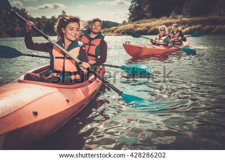 Happy best friends having fun on a kayaks