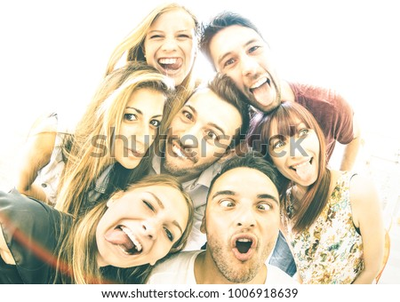 Happy best friends taking selfie outdoors with backlighting - Friendship concept with young people having fun together - Warm vintage filter with focus on face expressions and soft sunshine halo flare