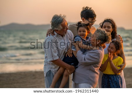 Happy big Asian family on beach holiday vacation. Multi-generation family holding hands and walking together on tropical beach at summer sunset. Family enjoy and having fun outdoor activity lifestyle.