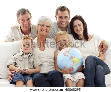 Happy big family on sofa holding a terrestrial globe