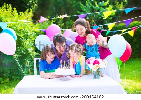 Happy big family with three kids - school age boy, toddler girl and a little baby enjoying birthday party with a cake blowing candles in a summer garden decorated with balloons and banners #200154182