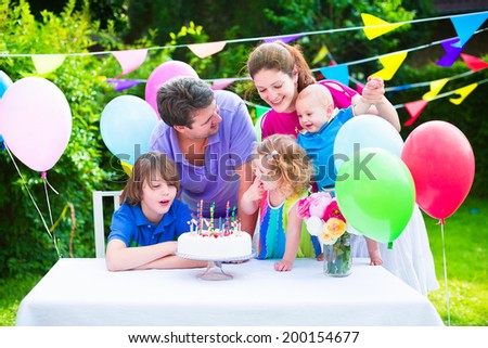 Happy big family with three kids - school age boy, toddler girl and a little baby enjoying birthday party with a cake blowing candles in a summer garden decorated with balloons and banners #200154677