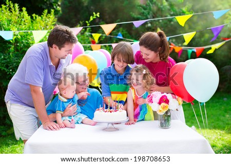 Happy big family young parents grandmother three kids teenage boy toddler girl and little baby celebrating birthday party with cake and candles in the garden decorated with balloons and banners
