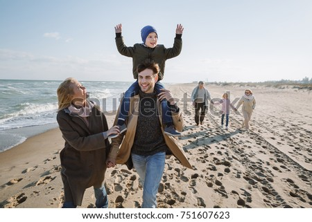 happy big multigenerational family walking together on seashore