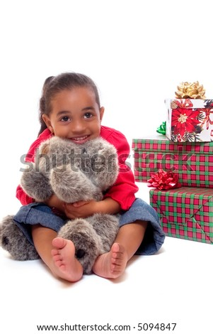 Happy biracial girl hugging a plush Christmas puppy with other wrapped gifts behind her.  Isolated on white.