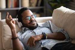Happy biracial millennial man in wireless headphones relax on couch at home listen to music, overjoyed African American male rest on sofa in living room enjoy good quality sound in modern earphones