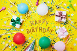 Happy birthday background or greeting flyer. Colorful holiday supplies on yellow table top view. Flat lay style.