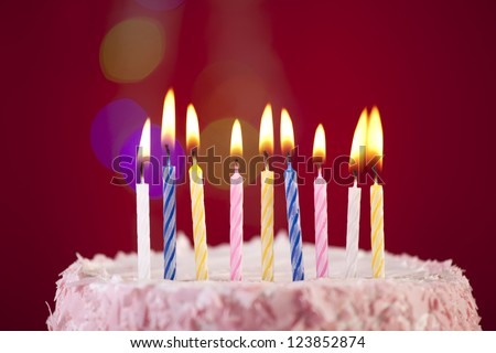 happy birthday cake shot on a red background with candles