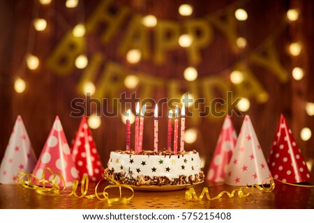 Happy birthday cake with candles on the background of garlands a #575215408