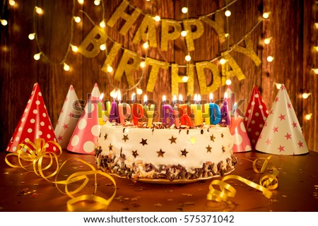 Happy birthday cake with candles on the background of garlands a #575371042