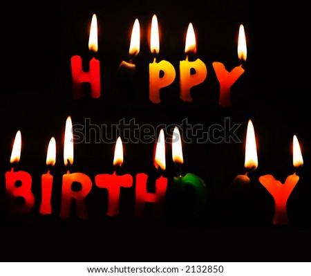 Happy Birthday candles alight against a dark background