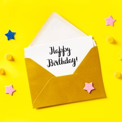 Happy Birthday card in a golden envelope, overhead square shot on a yellow background with glitter stars