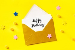 Happy Birthday card in a golden envelope, shot from above on a yellow background with glitter stars